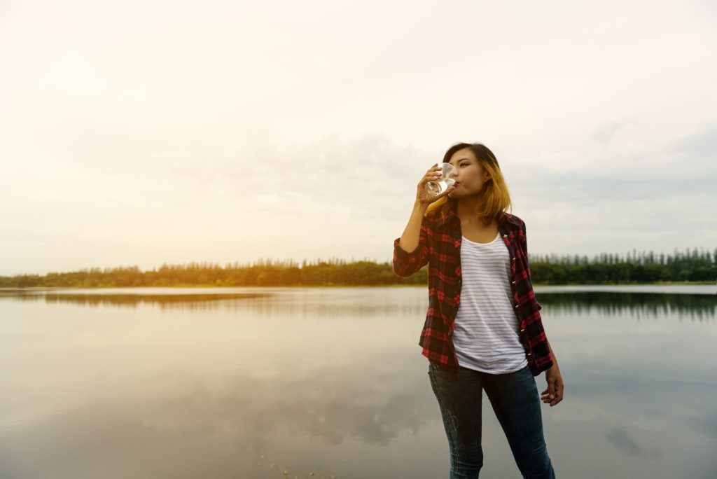 Beautiful young woman drinking water - beautiful happy woman enj