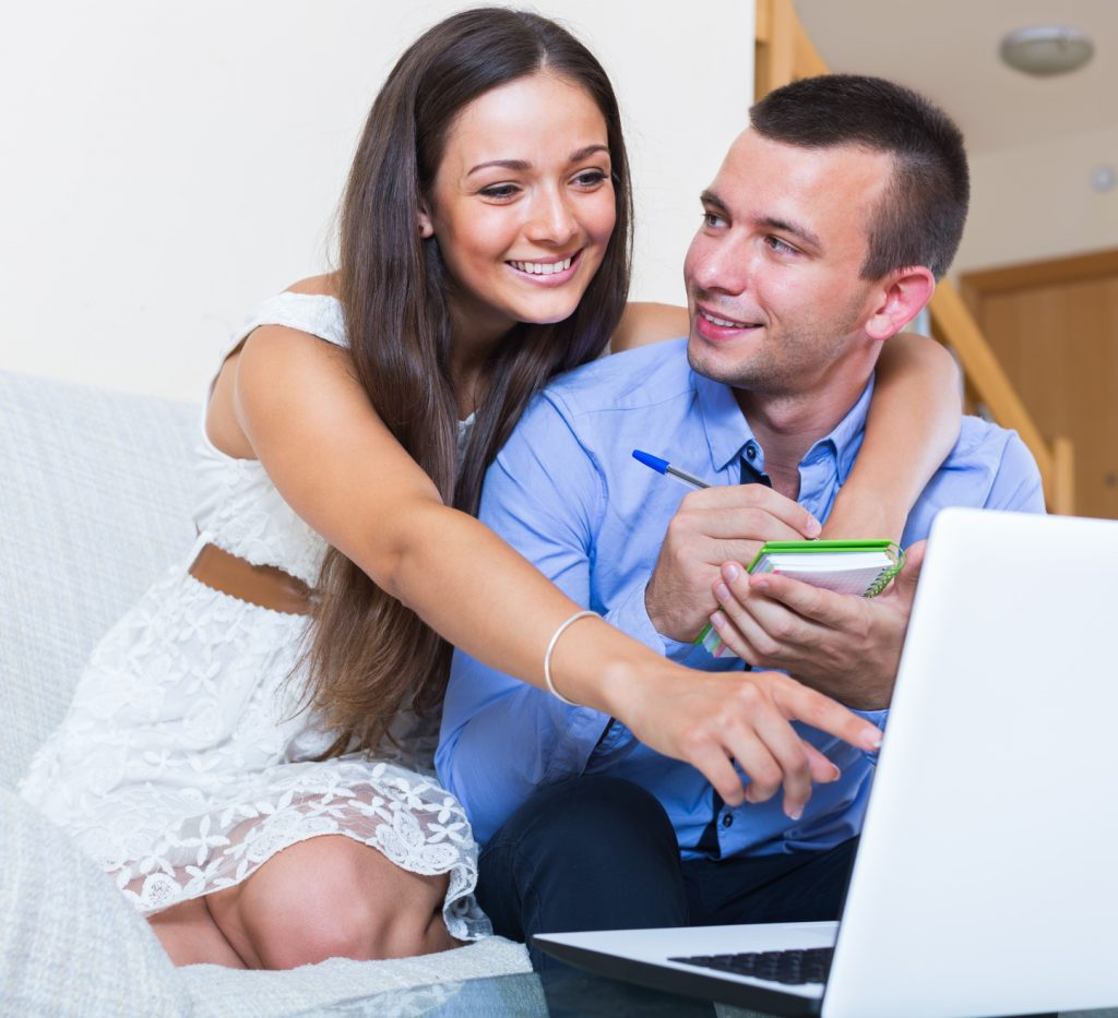 Couple making list for shopping online