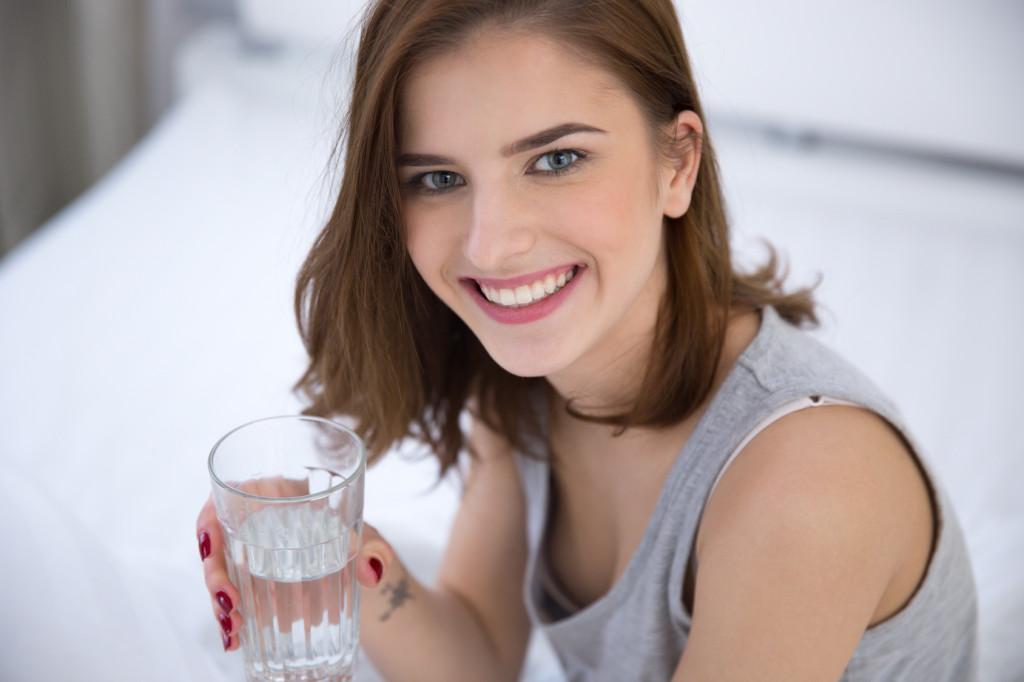 Happy woman drinking alkaline water