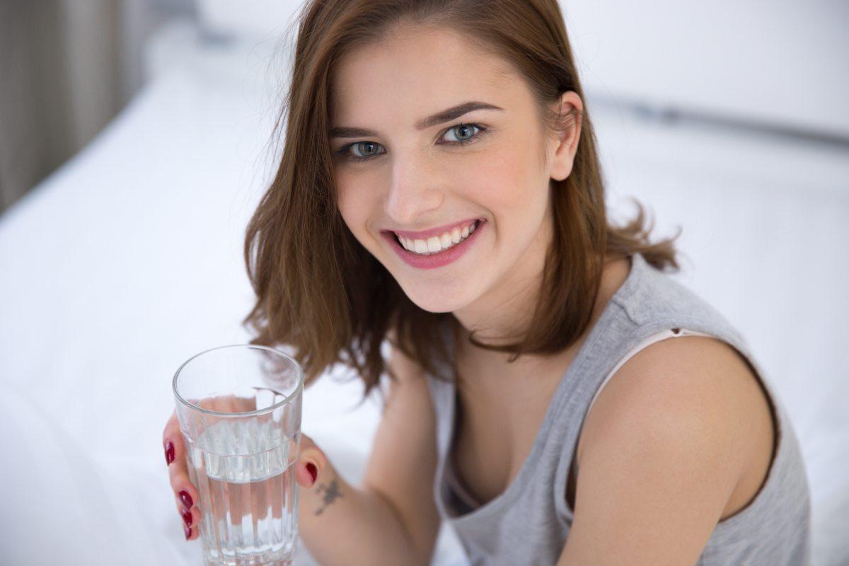 Happy woman drinking alkaline water | Alkaline Water And Urine