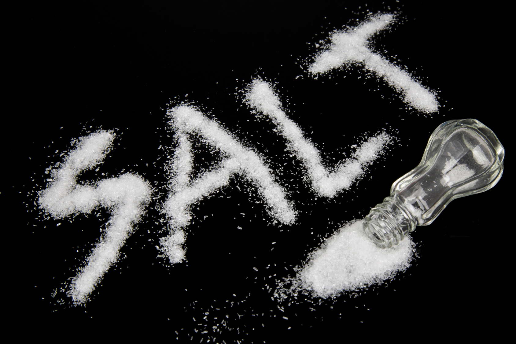 Salt spilled on a table and the word salt written out with the grains of the spice