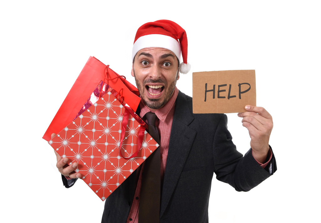businessman in Santa Claus Christmas hat holding shopping bags help sign overwhelmed tired and  in stress