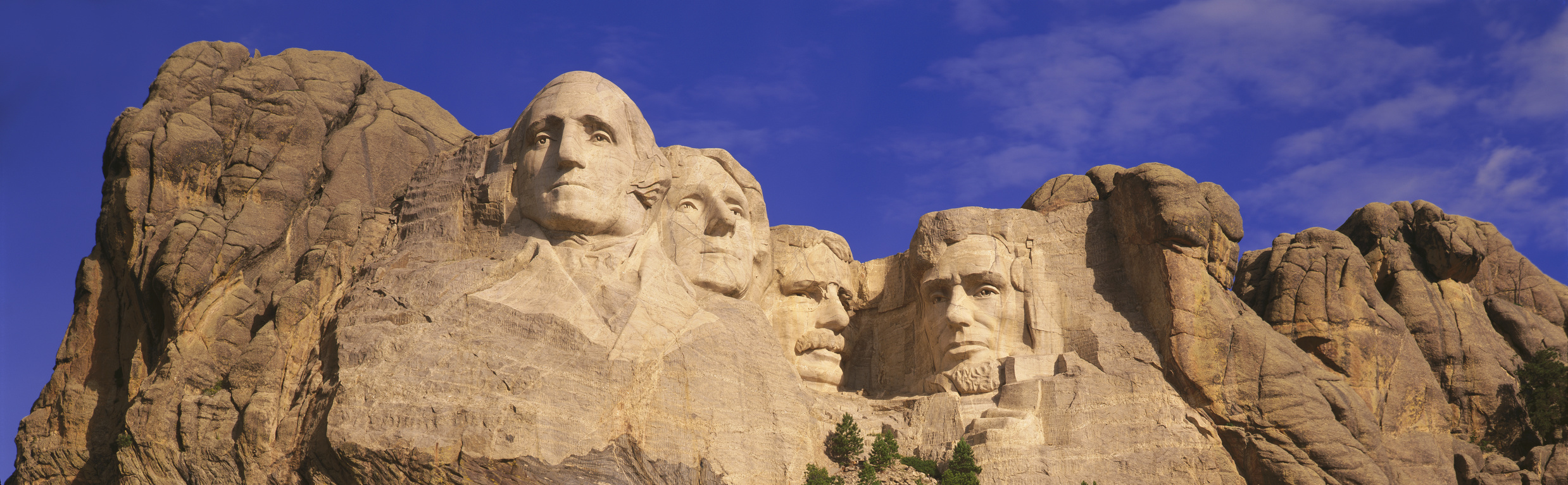 This is a close up view of Mount Rushmore National Monument against a blue sky. It shows the four faces of George Washington, Thomas Jefferson, Theodore Roosevelt, and Abraham Lincoln.