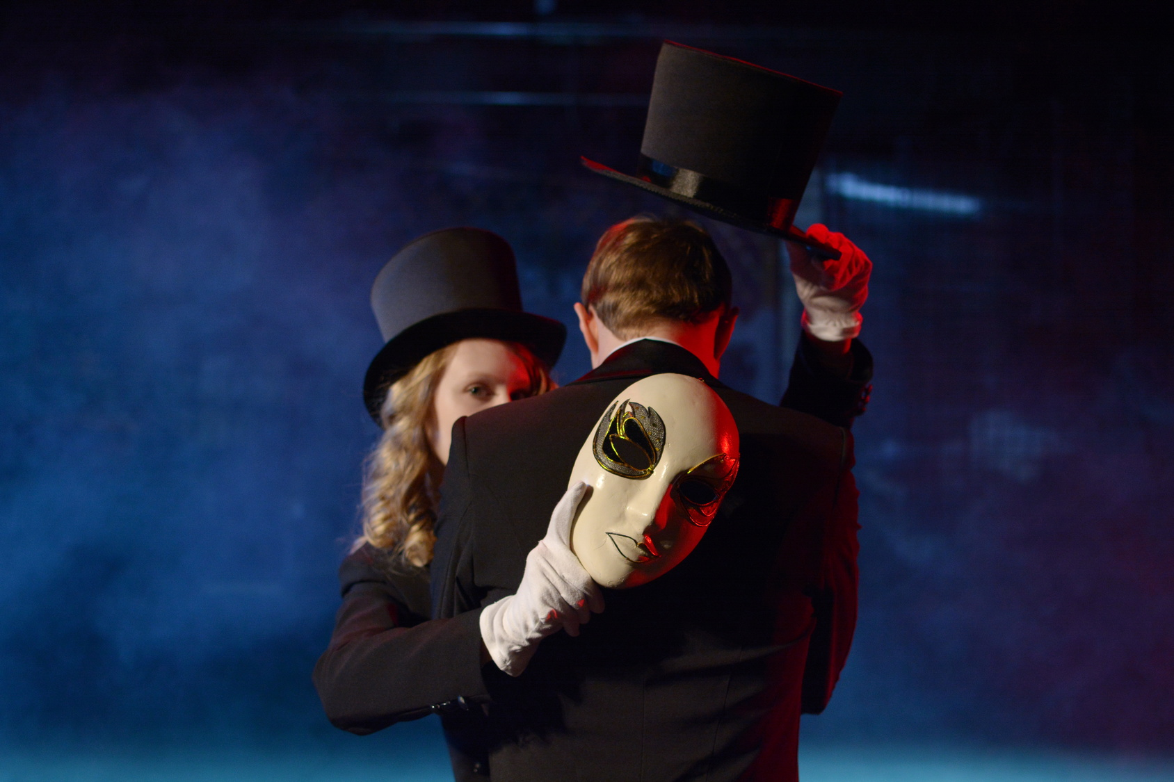 man and woman dancing in tuxedos and holding a theatrical mask