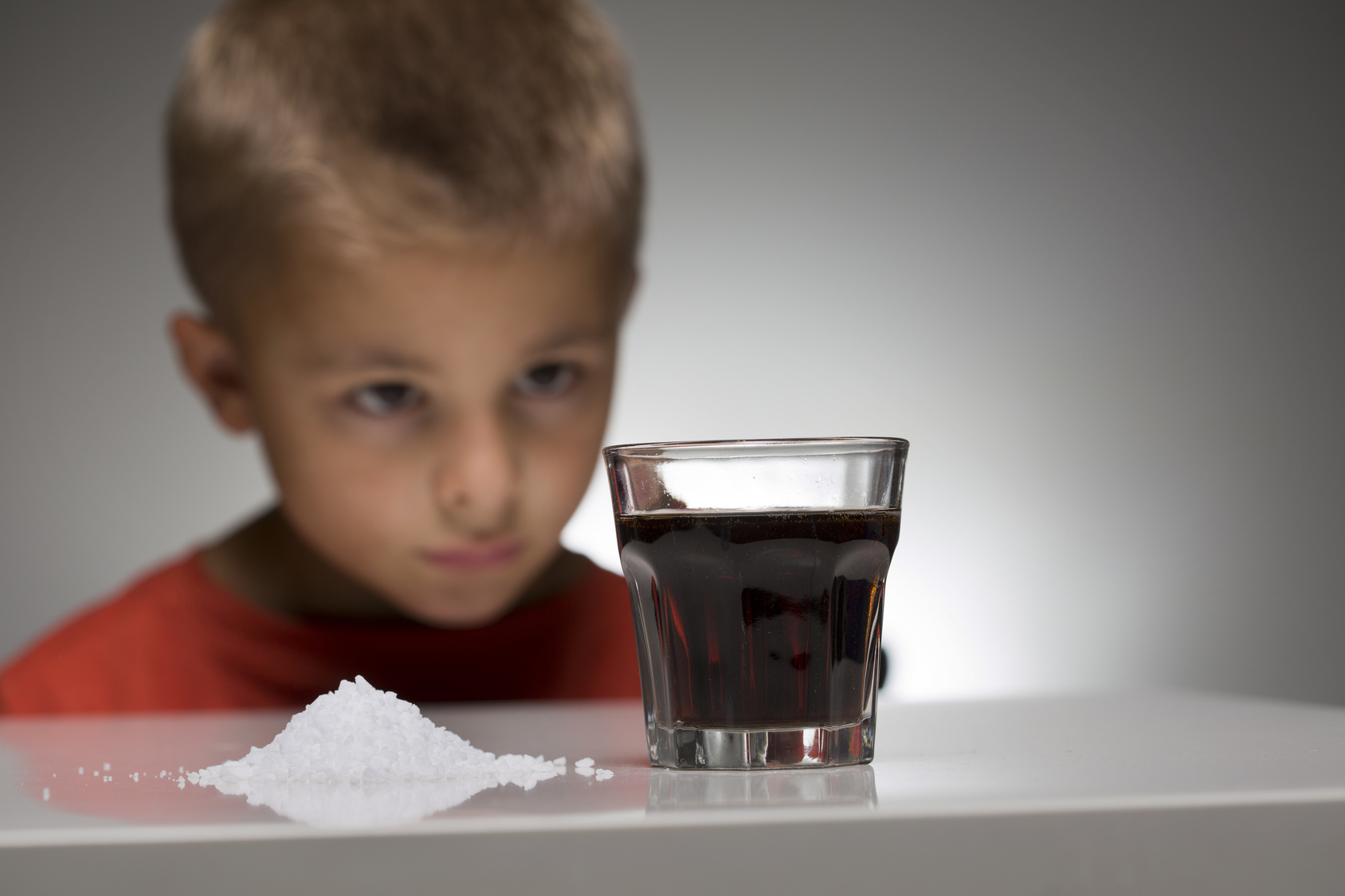 Concept photo of a child in front of a soft drink with sugar. The over-consumption of sugar-sweetened soft drinks is associated with obesity, type 2 diabetes, dental caries, and low nutrient levels.