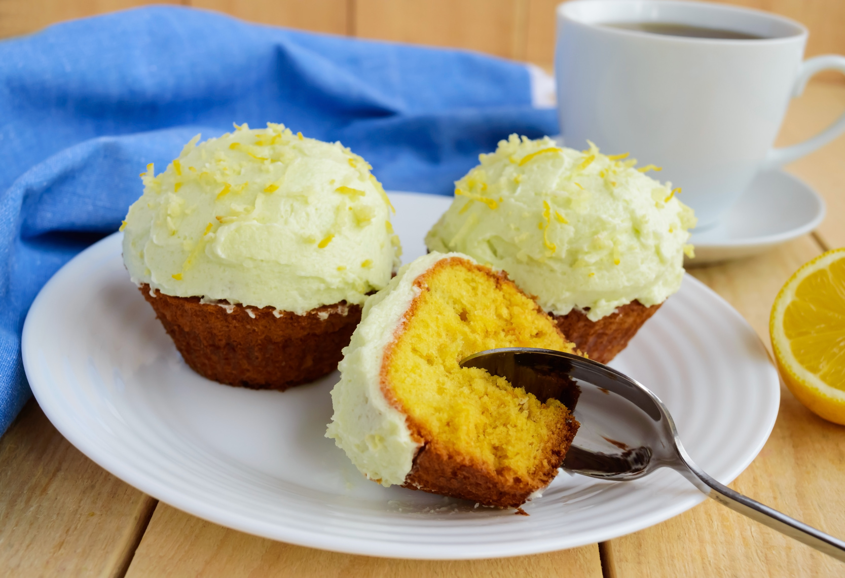 Light lemon cupcakes muffins on wooden background and a cup of tea.