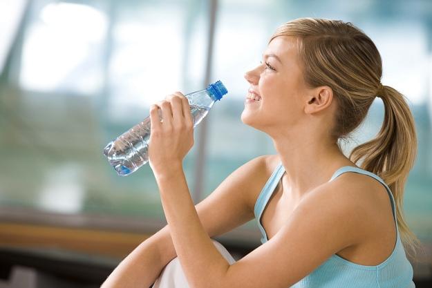 Beautiful woman holding bottles drinking water | Reasons to Love Tyent Water Ionizers | press