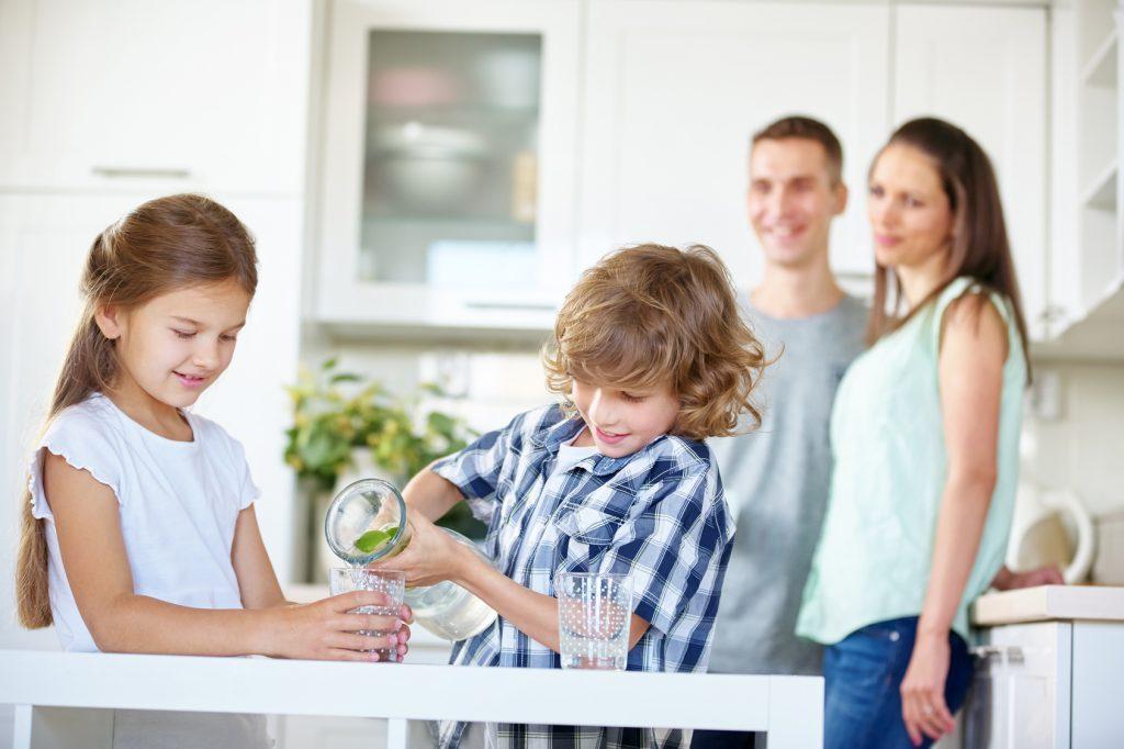 Zwei Kinder trinken Wasser mit frischen Limetten