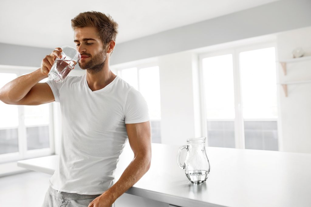 Handsome Man Drinking Glass Of Fresh Water Indoors In Morning