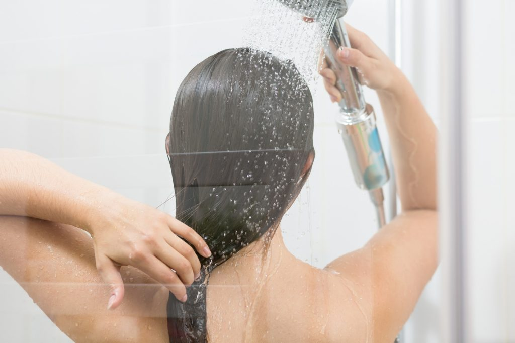 Girl washing hair under shower