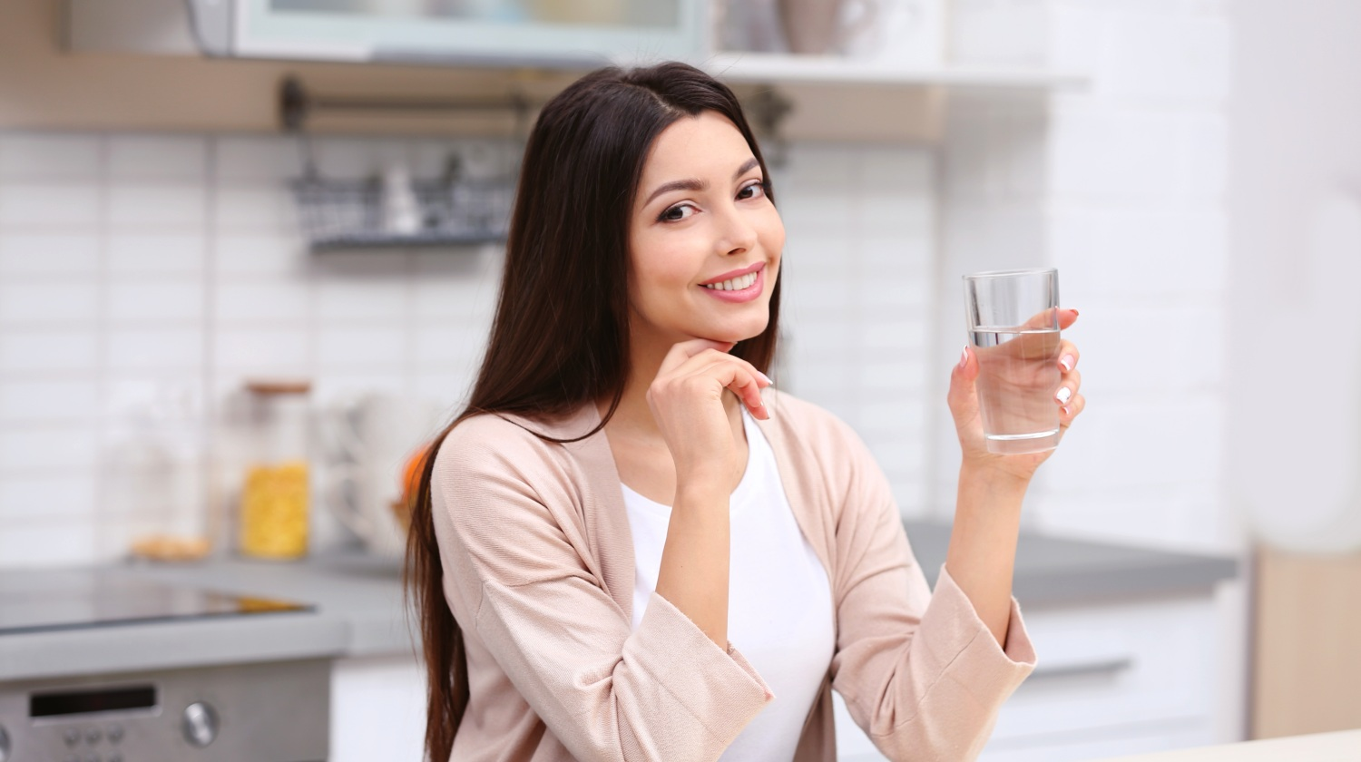 Feature | Woman holding a glass of water in the kitchen | Reasons to Love Tyent Water Ionziers, Part 9: Tyent Alkaline Water Is The Healthiest Water In The World. Dare To Compare! | healthiest water to drink