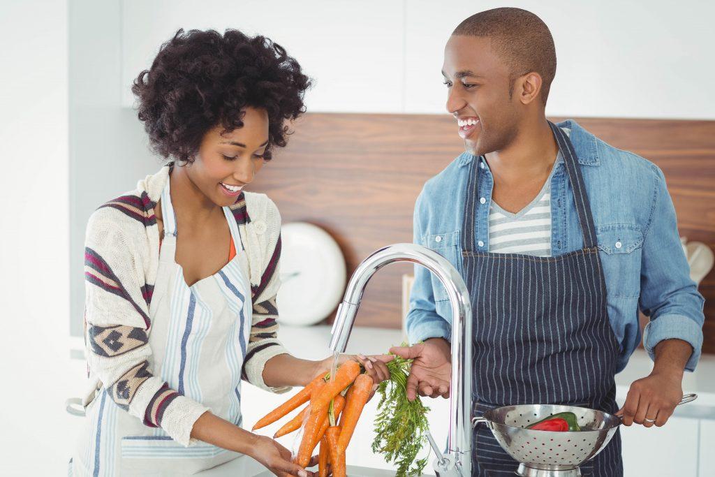 Happy couple washing vegetables