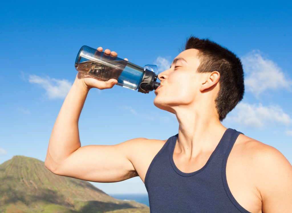 Young fit male drinking water.