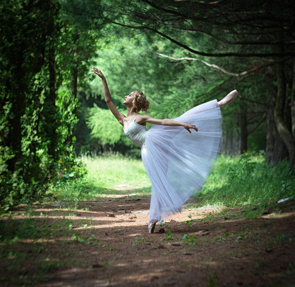 Dancing ballerina in the summer garden