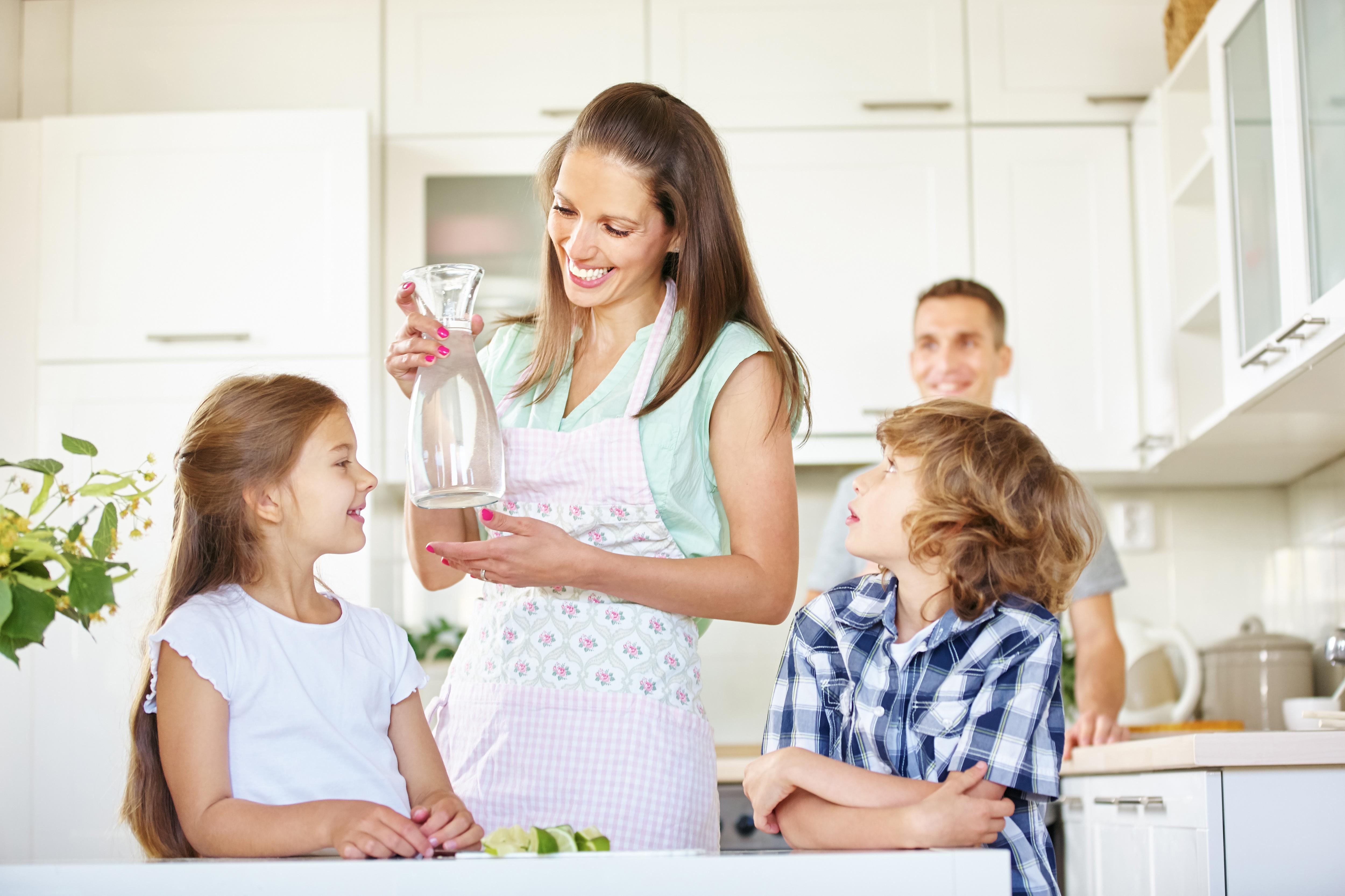 Mutter und Kinder mit einer Karaffe