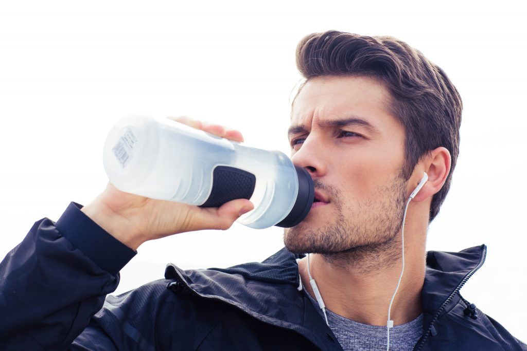 Handsome man in headphones drinking water