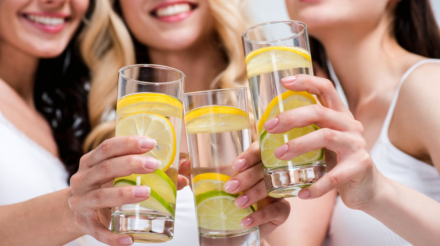 Feature | Young smiling woman clincking glasses water | Alkaline Water and Antioxidants