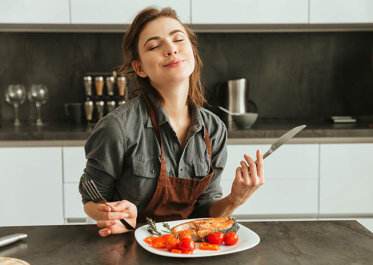 Pretty young woman sitting kitchen | Everything You Need To Know About Healthy Eating