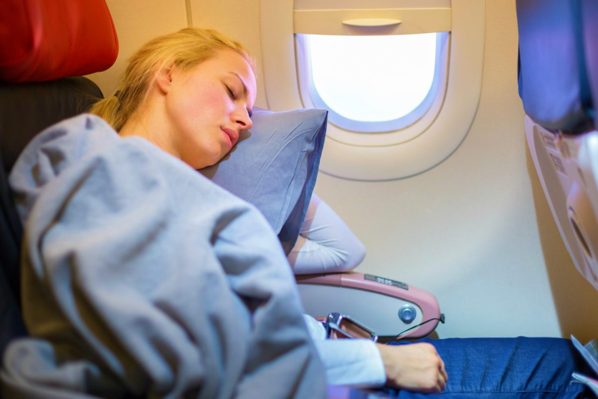 Tired blonde casual caucasian lady napping on uncomfortable seat while traveling by airplane | Travel Essentials For A Healthy Holiday
