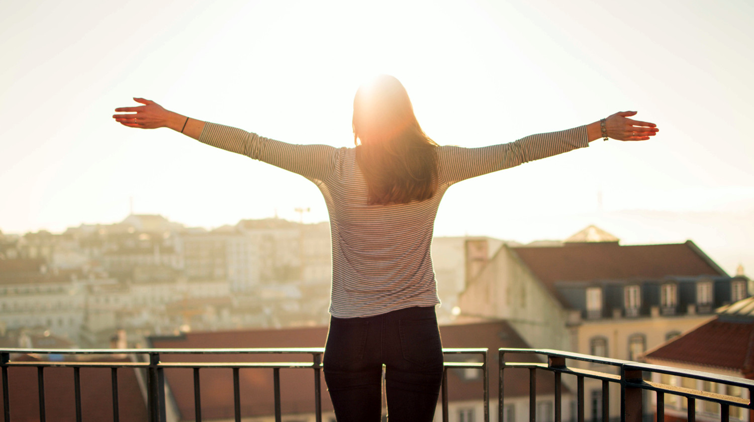 Feature | Balcony person standing sunshine | Morning Routine Hacks That Will Make Life Easier
