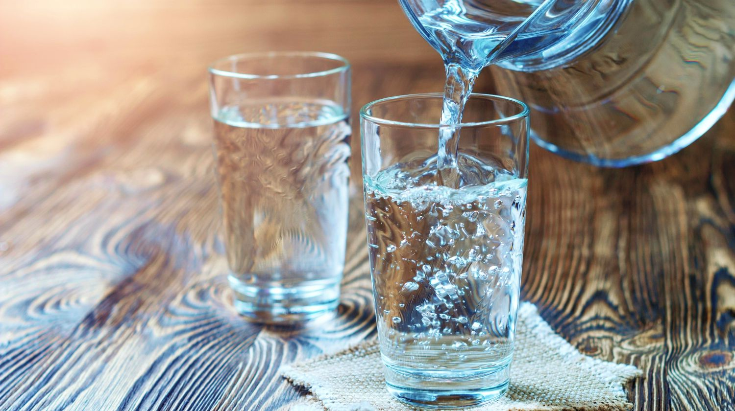 Feature | Glass of water on a wooden table. Water was poured into the beaker | Can You Drink Distilled Water | Uncovering the Truth