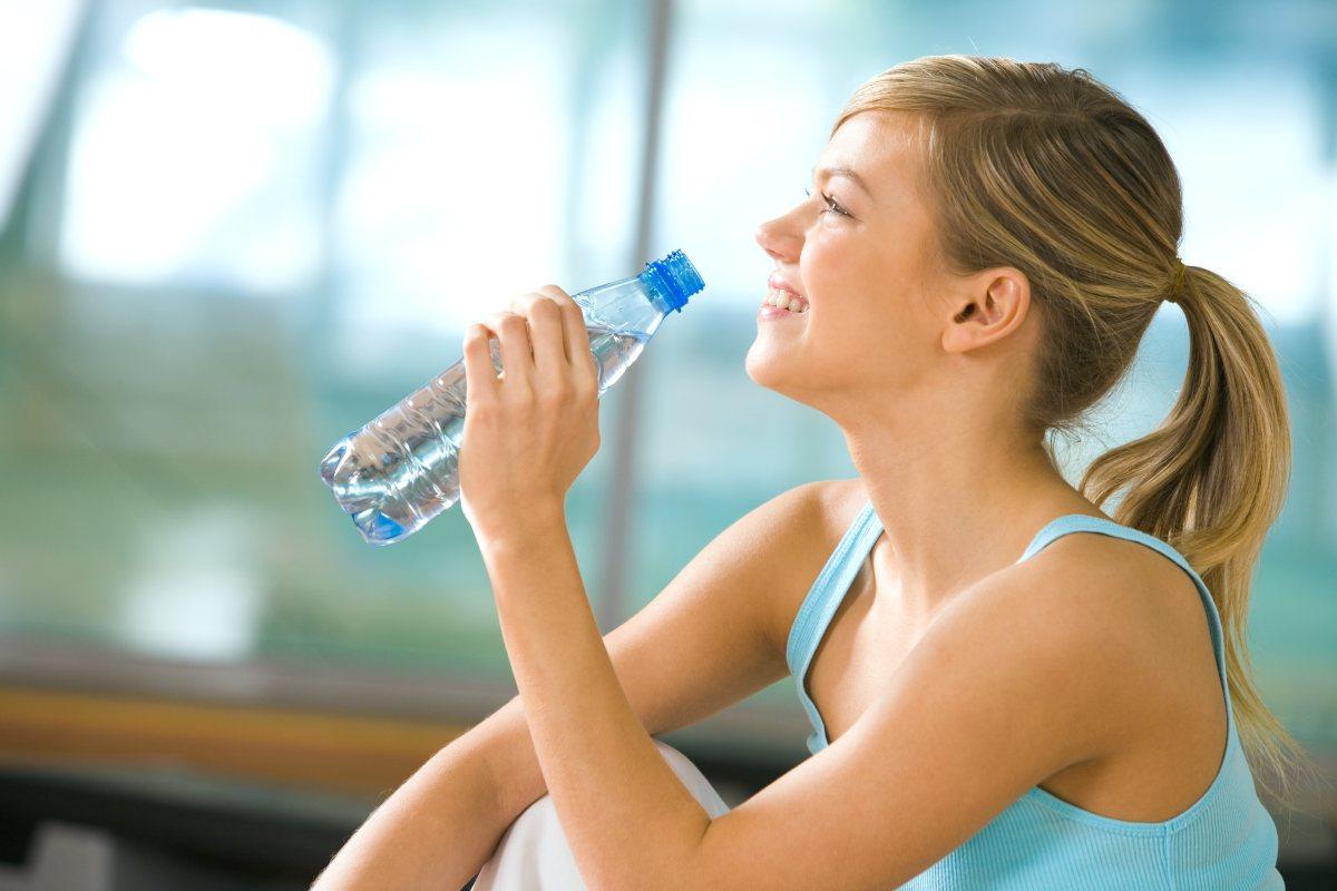 Beautiful woman holding bottles drinking water   Reasons to Love Tyent Water Ionizers   press