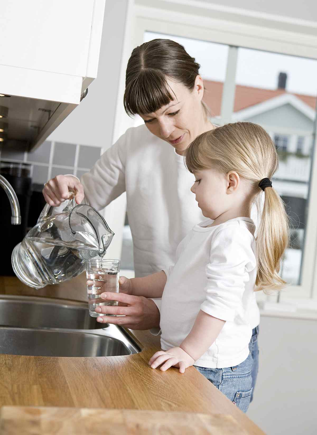 Mother pouring water on a glass with her daughter | Tyent Alkaline Water Ionizer Company Has Much to Offer You