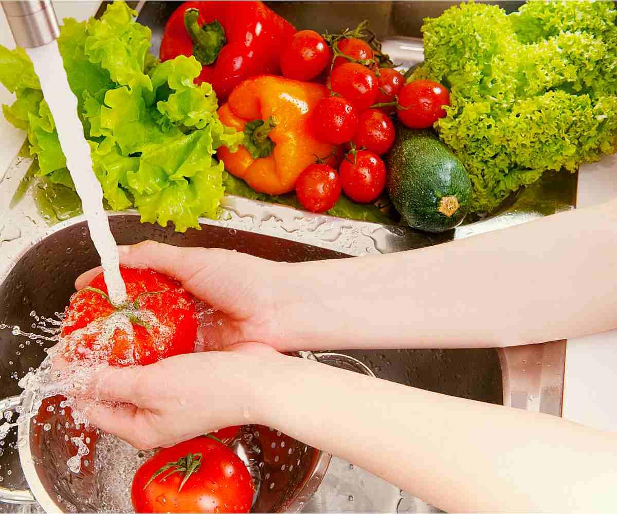 Fresh vegetables under water stream in colander | Kitchen Hacks Using Alkaline Water