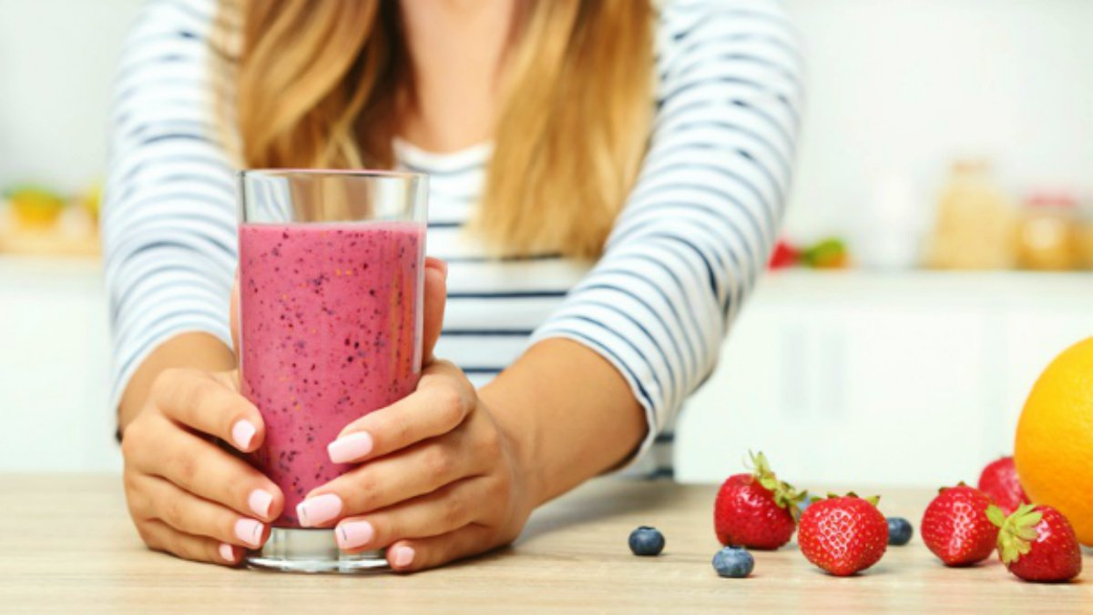 Young woman drinking smoothie kitchen | | Ways To Drink More Water This Year