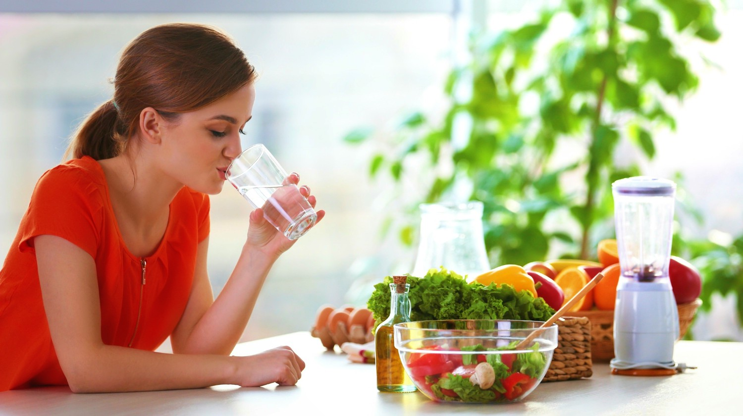 Young woman drinking water near table with fruits and vegetables in the kitchen | High Alkaline Foods To Add To Your Diet