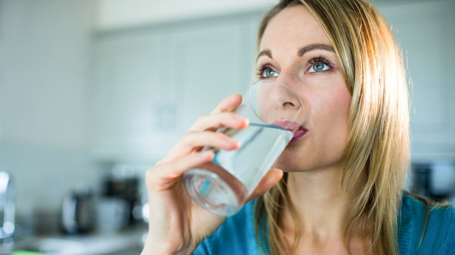 Feature | Pretty blonde woman drinking a glass of water at home | Why You Should Drink Hydrogen Water Instead of Purified Water