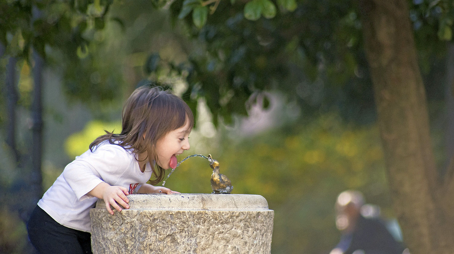 Feature | Girl thirsty drink fountain water | Is it Safe to Drink from a Public Water Fountain?