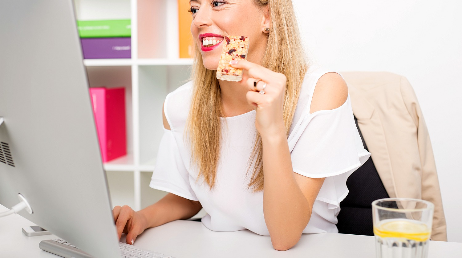 Feature | Woman eating protein bar at the office | Tasty Alkaline Recipes To Make At Home