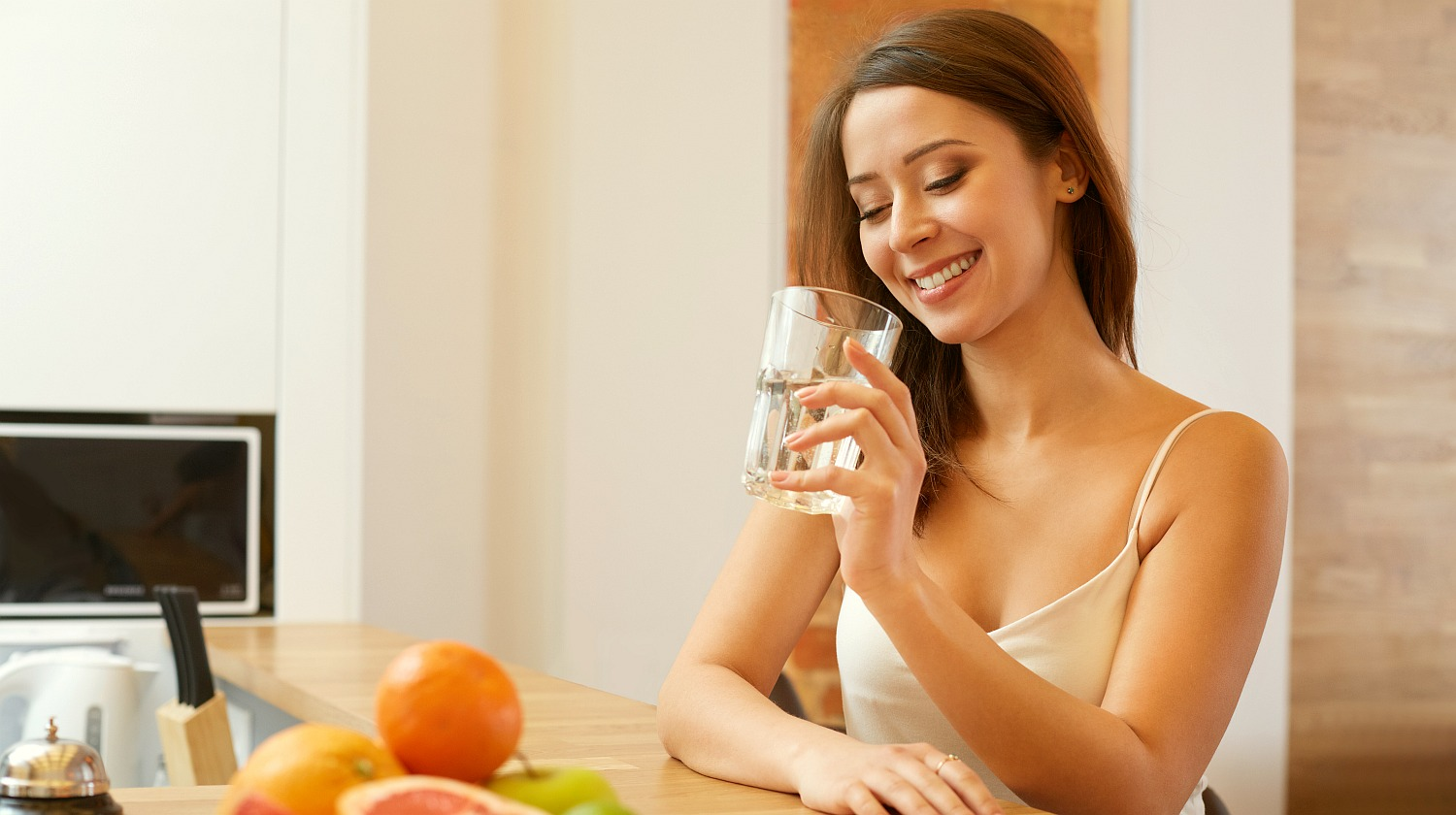 Feature | Beautiful woman holding glass with water | What Exactly Is pH Level and Why Should I Care?