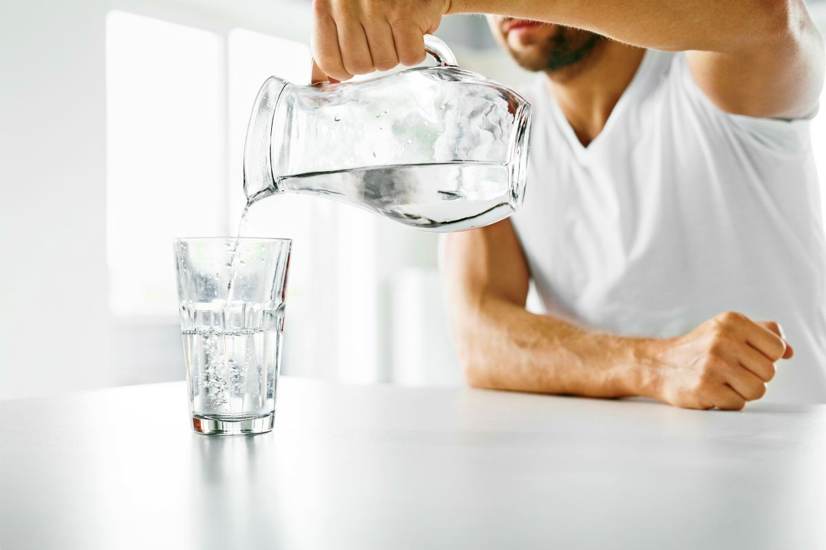 man pouring water | Can Drinking Water Improve Your Gut Health? | leaky gut syndrome